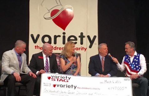 Rick Ball helps present a $147,000 check to Variety Iowa